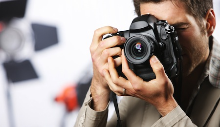 Young man taking photo with professional digital camera focus on hand and lens