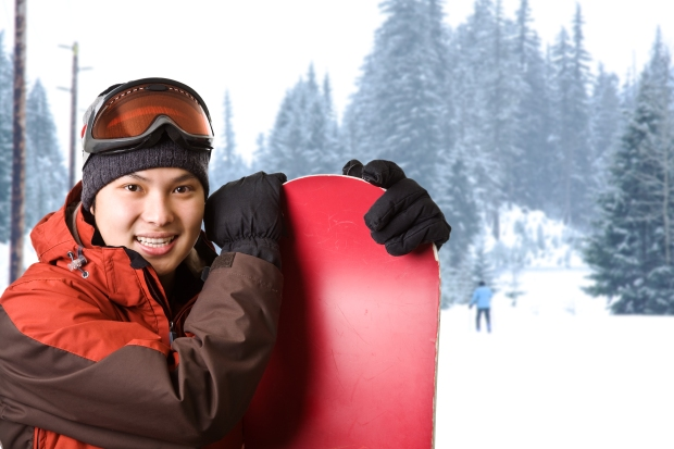 A shot of an asian snowboarder at a ski resort